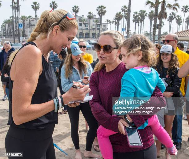 Olympic gold medalist Kerri Walsh Jennings signs a photograph for Amy Allison and her daughter Savannah of Huntington Beach following a ceremony in...