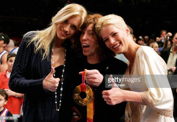 Olympic gold medalist Shaun White poses with models Jennifer Ohlsson and Jessica Van der Steen before the start of the game between the Miami Heat...