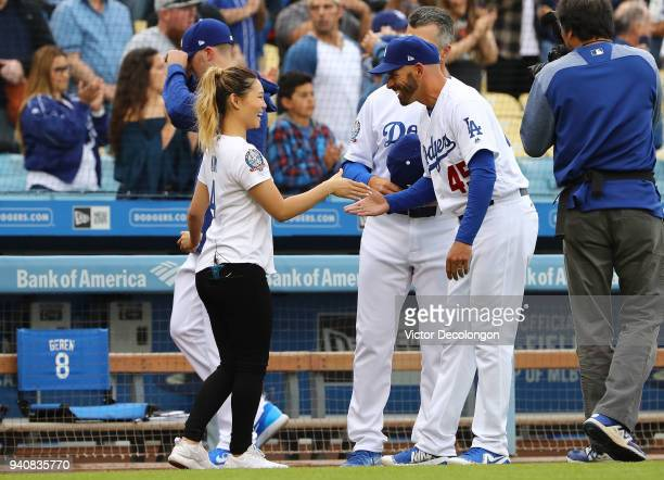 S Olympic gold medalist snowboarder Chloe Kim shakes hands with coach Chris Woodward of the Los Angeles Dodgers after the singing of the National...