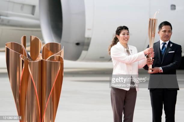 Olympic gold medalists Tadahiro Nomura and Saori Yoshida hold the Olympic torch before lighting the Olympic flame during the Tokyo 2020 Olympic Games...