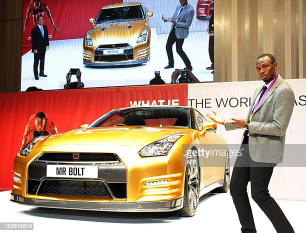 Olympic gold medallist Usain Bolt of Jamaica poses for a photo in front of Japanese auto giant Nissan's gold coloured sports car GTR at Nissan's...