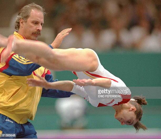 Olympic gymnast Gina Gogean of Romania is helped by coach Bellu Octavian as she practices her floor exercises at the Georgia Dome in Atlanta 16 July....