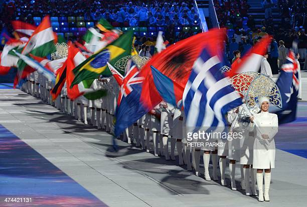 Olympic hostesses wave the flags of participating nations during the Closing Ceremony of the Sochi Winter Olympics at the Fisht Olympic Stadium on...