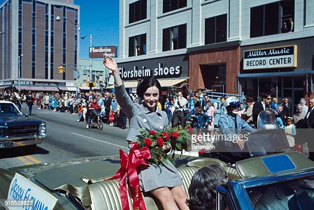 Olympic ice skater Peggy Fleming waving to crowd from open car during parade in her honor following her homecoming