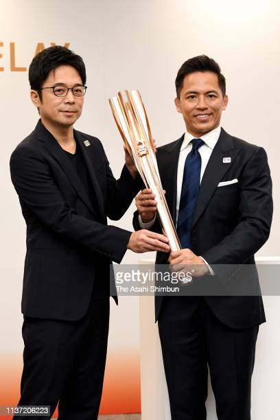 Olympic Judo three-time gold medalist Tadahiro Nomura and designer Tokujin Yoshioka unveil the Tokyo 2020 Olympic Games torch during its unveiling...