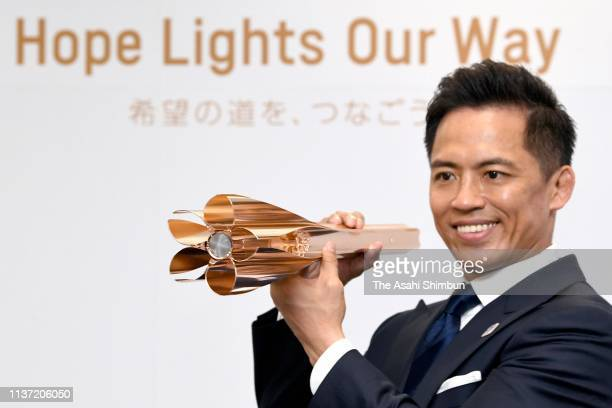 Olympic Judo three-time gold medalist Tadahiro Nomura unveils the Tokyo 2020 Olympic Games torch during its unveiling press conference on March 20,...