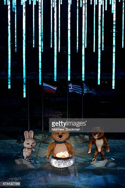 Olympic mascots the Hare, the Polar Bear and the Leopard stand by the Olympic flame during the 2014 Sochi Winter Olympics Closing Ceremony at Fisht...