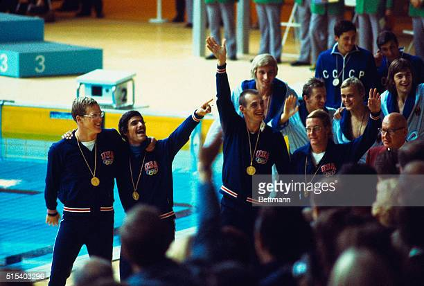 US Olympic men's 4X200 meter relay team waving to the crowd and wearing their gold medals after they won the race They are left to right John...