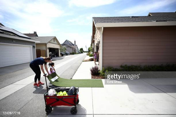 Olympic softball pitcher Monica Abbott places the pitching mound on the street behind her house with the help of child that lives nearby during a...