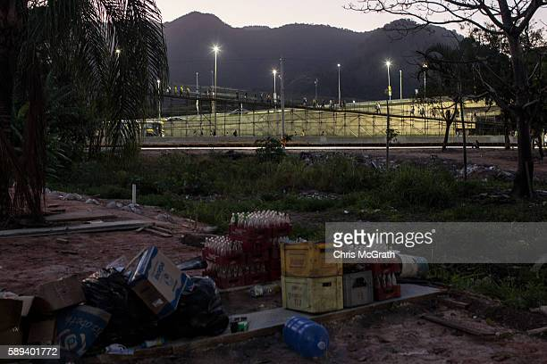 Olympic spectators walk to Olympic Park via an overpass as items left from demolished houses in the former Vila Autodromo 'favela' community are seen...