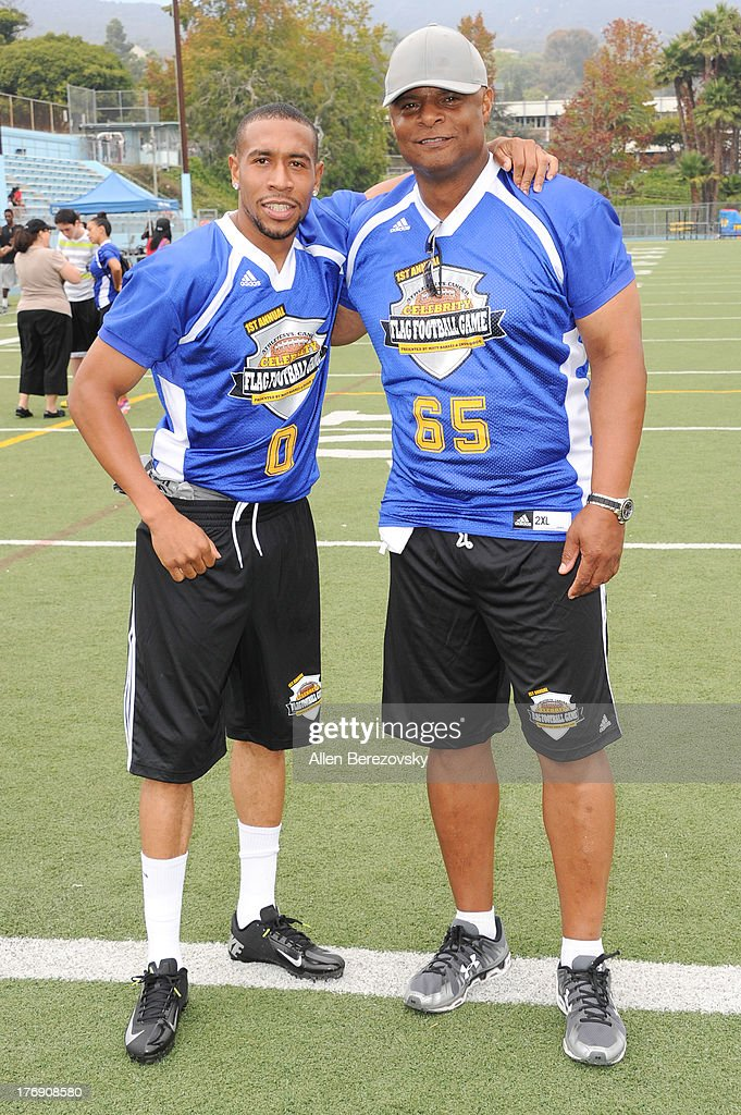 Olympic sprinter Bryshon Nellum (L) and former NFL player Warren Moon participate in the 1st Annual Athletes VS Cancer Celebrity Flag Football Game on August 18, 2013 in Pacific Palisades, California.