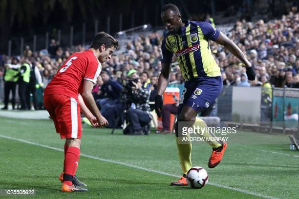 Olympic sprinter Usain Bolt , playing for A-League football club Central Coast Mariners, fights for the ball with a player from a Central Coast...