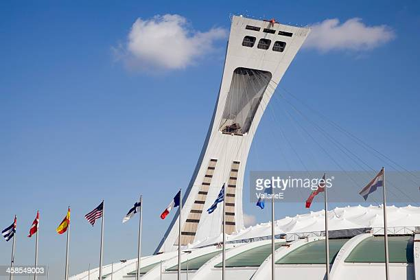 olympic stadium with flags - montreal olympic stadium stock photos and pictures
