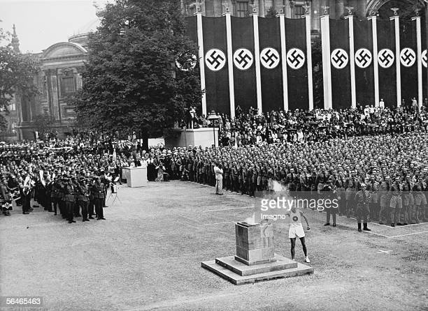 XI Olympic Summer Games in Berlin in 1936 The finisher lights the olympic fire with his torch in the Lustgasse 1st of August 1936 Photography [XI...