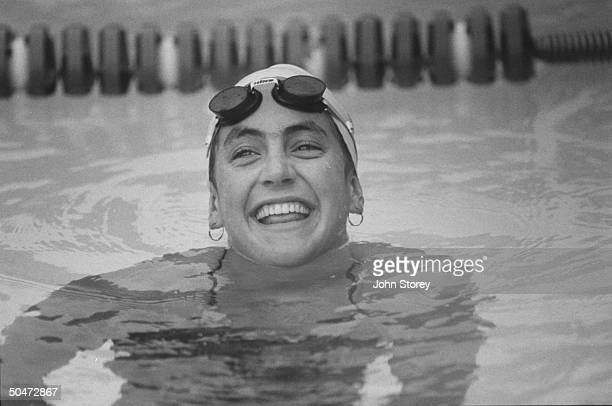 US Olympic swimmer Summer Sanders wearing bathing cap w goggles pushed up on forehead treading water in pool during practice session at Stanford Univ...