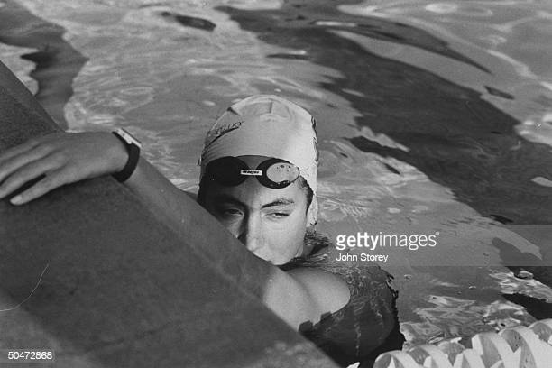 US Olympic swimmer Summer Sanders wearing bathing cap w goggles pushed up on forehead resting at the edge of pool during practice session at Stanford...