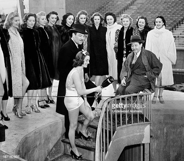 Olympic swimming star Eleanor Holm is ready to crack a bottle of champagne to christen the new 275 foot swiming pool at the New York World's Fair,...