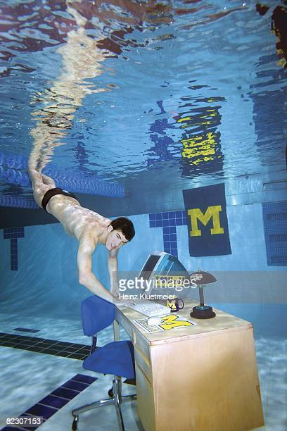 Underwater portrait of Olympian and U of Michigan student Michael Phelps swimming to study lounge computer at Canham Natatorium on University of...