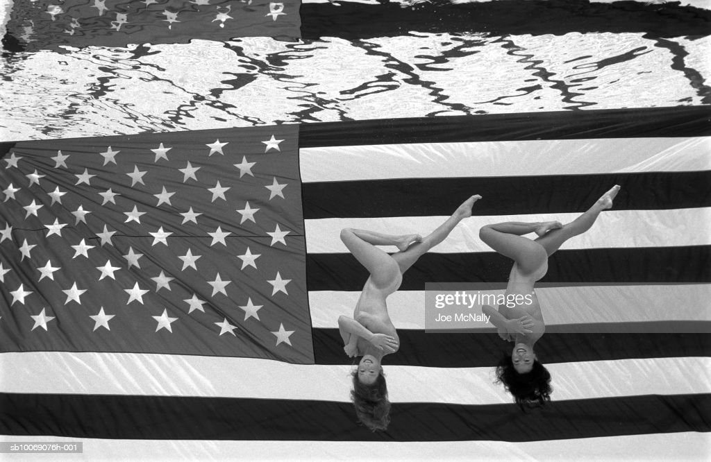 USA, Georgia, Atlanta, naked Olympic synchronized swimmers on American flag, directly above, portrait : News Photo