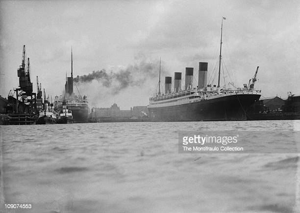 RMS Olympic the first of three ocean liners built by Harland and Wolff's shipbuilders Belfast for the White Star Line in dock alongside large ship...