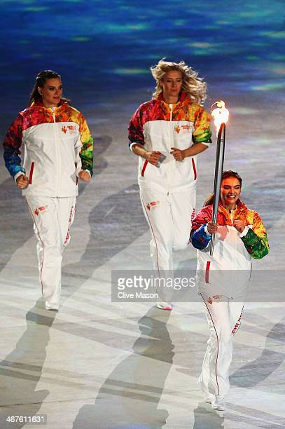 Olympic torch bearer Alina Kabaeva carries the torch with Maria Sharapova and Elena Isinbaeva during the Opening Ceremony of the Sochi 2014 Winter...