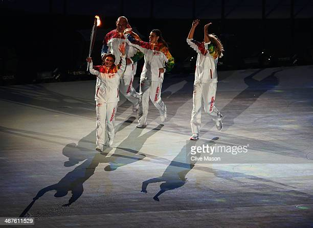 Olympic torch bearer Alina Kabaeva carries the torch with Maria Sharapova Alexandr Karelin and Elena Isinbaeva during the Opening Ceremony of the...
