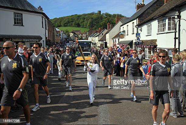 Olympic torchbearer Katrina Doyle runs with the Olympic flame through Dunster on May 21 2012 near Minehead England The Olympic Flame arrived in the...