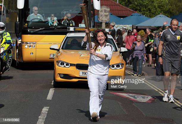 Olympic torchbearer Sarah Milner Simonds runs with her olympic torch which she has already sold on the online auction site eBay for 153100 GBP as she...
