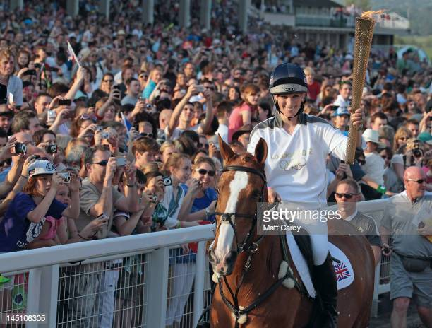 Olympic torchbearer Zara Phillips arrives on her horse Toy Town as she brings Olympic flame to Cheltenham Racecourse on May 23 2012 in Cheltenham...