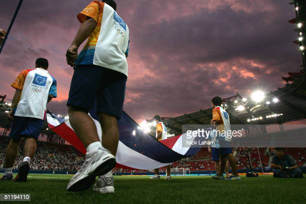Olympic volunteers carry the Coasta Rica flag onto the playing field during the men's football preliminary match on August 15, 2004 during the Athens...