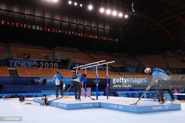 Olympic volunteers clean the venue during Men's Podium Training ahead of the Tokyo 2020 Olympic Games at Ariake Gymnastics Centre on July 21, 2021 in...