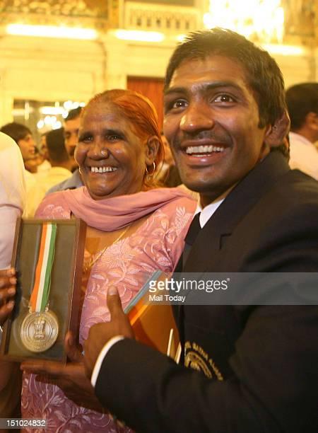 Olympic wrestler Yogeshwar Dutt poses with his mother Sushila Devi after receiving Rajiv Gandhi Khel Ratna 2012 award at President's House in New...