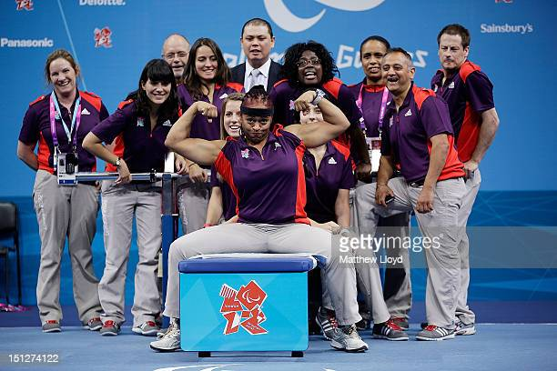 Olympics volunteers have their pictures taken with the weights bench between sessions on the final day of powerlifting, day 7 of the London 2012...