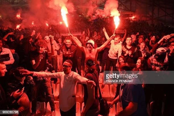 Olympique de Marseille fans burn flares as they watch the UEFA Europa League final football match between Olympique de Marseille and Club Atletico de...