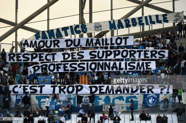 TOPSHOT Olympique de Marseille fans hold a banner reading 'for the love of the OM jersey the respect of fans and professionalism is it too much to...