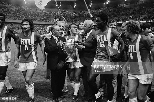 Olympique de Marseille player Georges Bereta holds his team's trophy as he is congratulated by team President Fernand Meric and Marius Tresor...