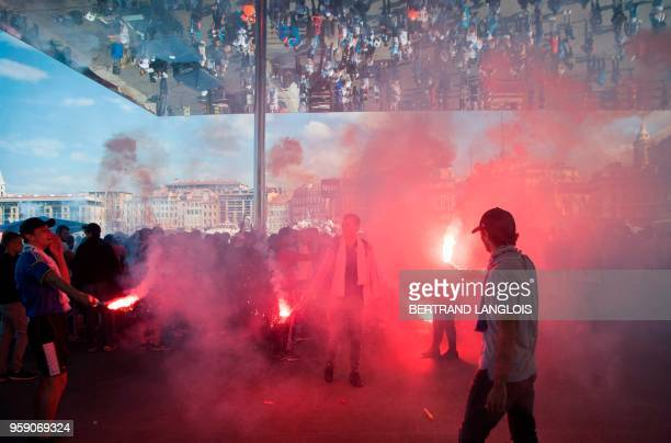 Olympique de Marseille supporters let off a flare as they cheer for their team in the Vieux Port in Marseille on May 16 ahead of the 2018 UEFA Europa...