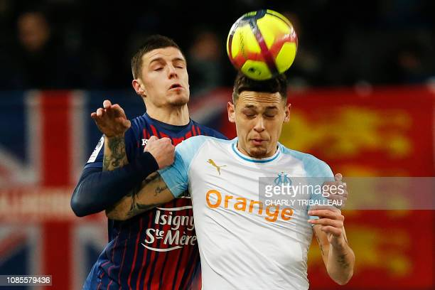 Olympique de Marseille's Argentinian forward Lucas Ocampos heads the ball past Caen's French defender Frederic Guilbert during the French L1 football...