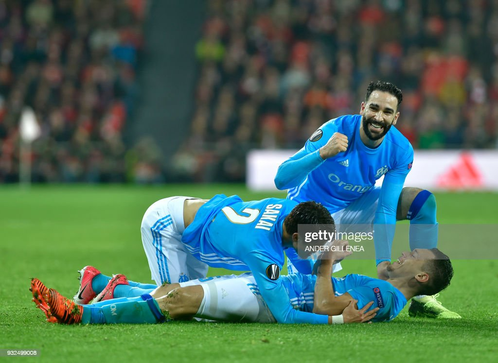 Olympique de Marseille's Argentinian midfielder Lucas Ocampos (BOTTOM) is congratulated by teammates Japanese defender Hiroki Sakai (L) and French defender Adil Rami after scoring his team's second goal during the UEFA Europa League round of sixteen second leg football match between Athletic Club Bilbao and Olympique de Marseille at the San Mames stadium in Bilbao on March 15, 2018. /