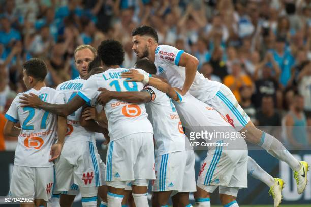 Olympique de Marseille's Cameroonian forward Clinton Njie is congratulated by Olympique de Marseille's teammates after scoring a goal during the...
