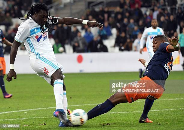 Olympique de Marseille's French forward Bafetimbi Gomis scores a goal as he vies with Montpellier's French defender William Remy during the French L1...