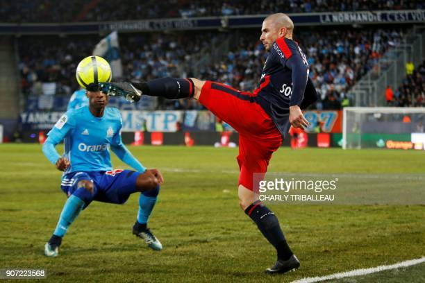 Olympique de Marseille's French forward Bouna Sarr vies for the ball with Caen's French midfielder Vincent Bessat during the French L1 football match...
