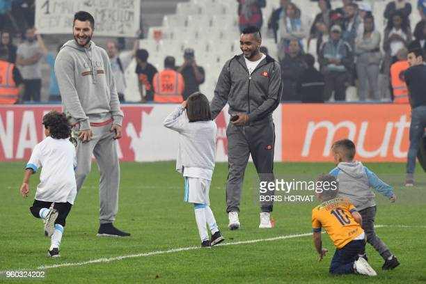 Olympique de Marseille's French forward Dimitri Payet and former forward French AndrePierre Gignac play football with children at the end of the...