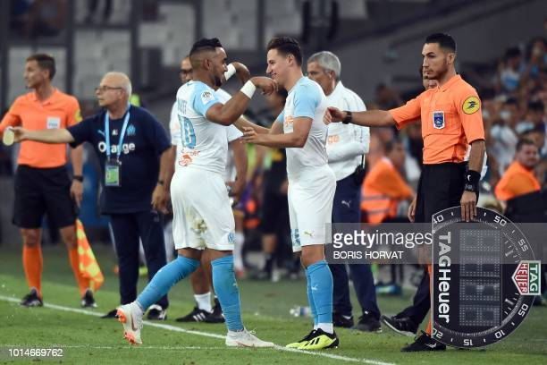Olympique de Marseille's French forward Dimitri Payet leaves the pitch as he his congratulated by Olympique de Marseille's French midfielder Florian...
