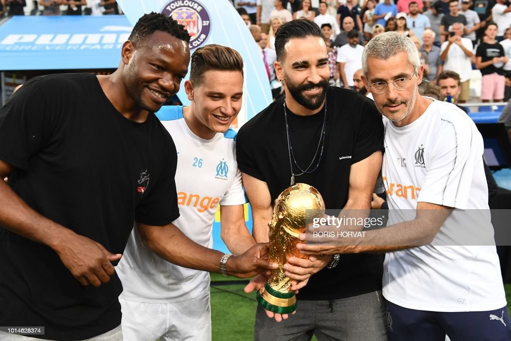 Olympique de Marseille's French goalkeeper Steve Mandanda, Olympique de Marseille's French midfielder Florian Thauvin, Olympique de Marseille's French defender Adil Rami and Olympique de Marseille's French doctor Franck Le Gall pose with the World Cup Trophy during the French L1 football match between Olympique de Marseille (OM) and Toulouse at the Velodrome stadium, in Marseille, on August 10, 2018.