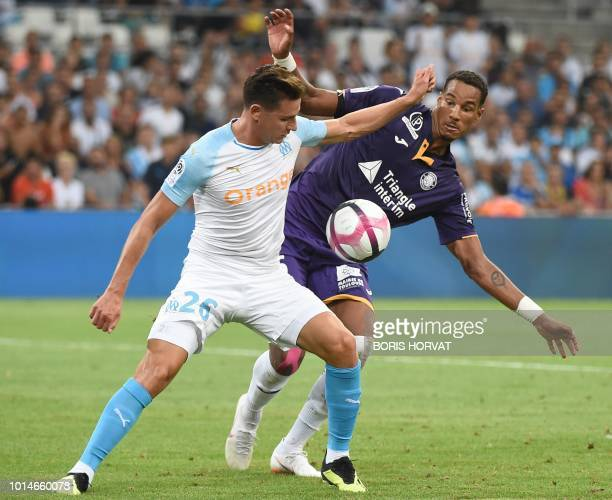 Olympique de Marseille's French midfielder Florian Thauvin competes for the ball with Toulouse's French defender Christopher Jullien during the...