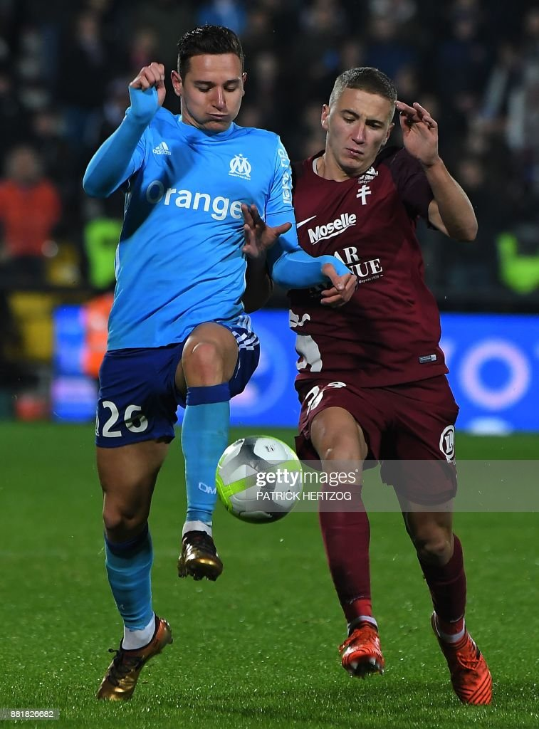 Olympique de Marseille's French midfielder Florian Thauvin (L) fights for the ball with Metz' French defender Nicolas Basin during the French Ligue 1 football match between Metz (FCM) and Marseille (OM) at the Saint-Symphorien stadium in Longeville-les-Metz, eastern France on November 29, 2017. /