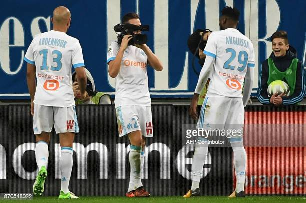 Olympique de Marseille's French midfielder Florian Thauvin films his teammates with a camera as he celebrates after scoring a goal during the French...
