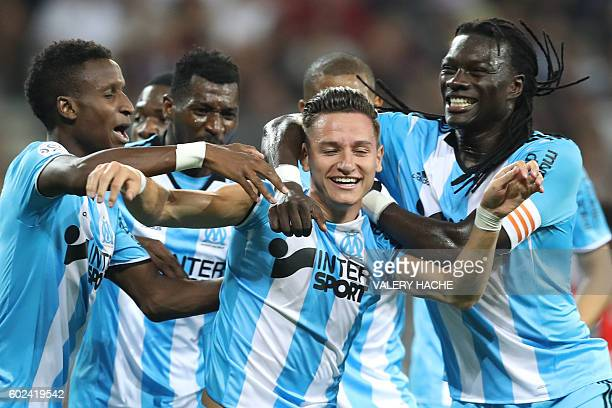 Olympique de Marseille's French midfielder Florian Thauvin is congratulated by teammates after scoring a goal during the French L1 football match OGC...