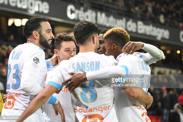 Olympique de Marseille's French midfielder Florian Thauvin is congratulated by teammates after scoring a goal during the French L1 football match...